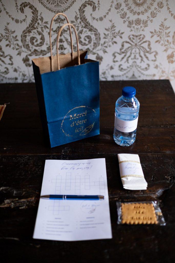 contenu du sac invité de mariage : bouteille d'eau pesonnalisée, biscuit personnalisé, mouchoirs, mots croisés et stylos à l'effigie des mariées